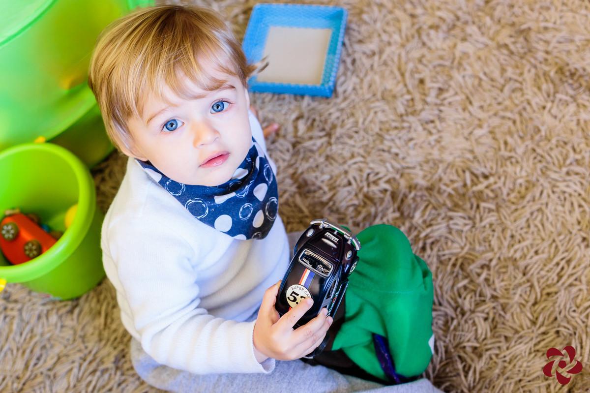 Otávio está sentando no tapeta da sala brincando com seus carrinhos e está olhando para a câmera com seus lindos olhos azuis.