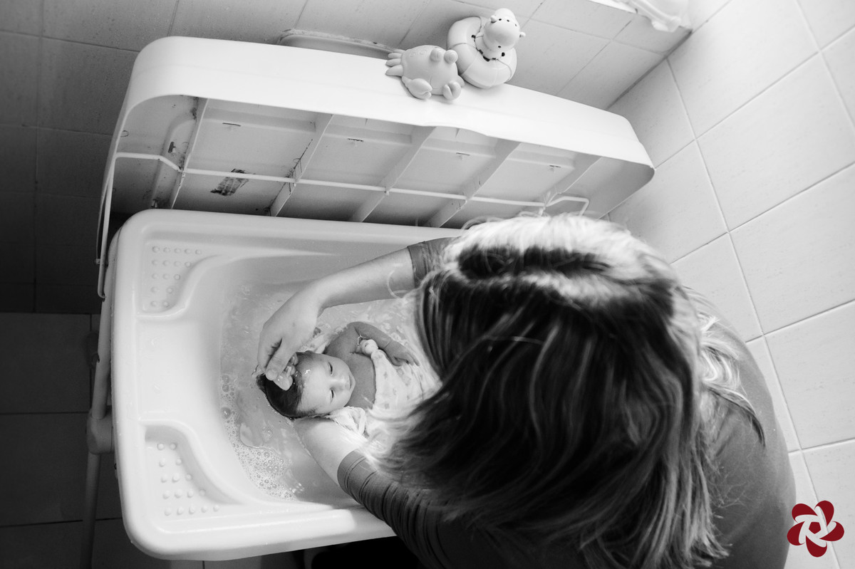 Natácia dá banho na Júlia na banheira. A foto mostra brinquedos em cima da tampa da banheira e a mãe lavando o cabelo da bebê.