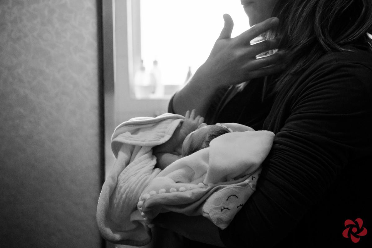 A mãe está com a filha no colo, enrolada em sua toalha de bebê.