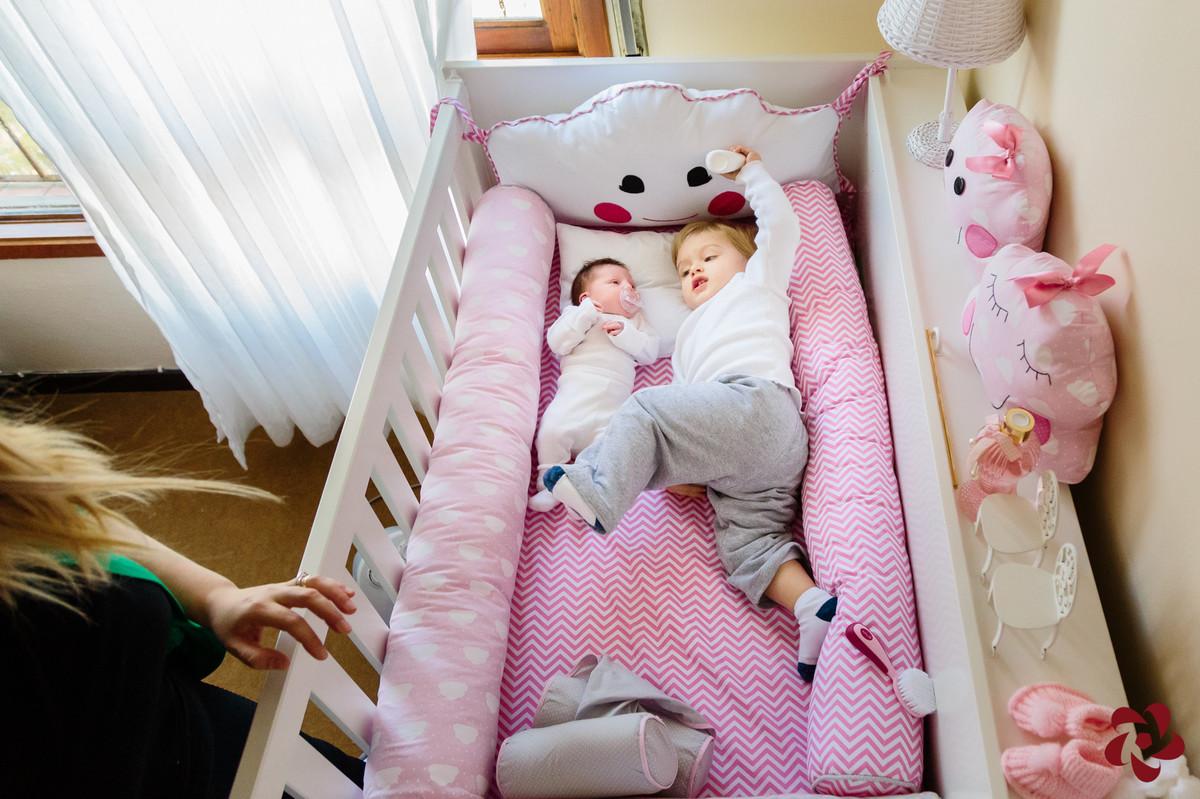 Júlia e Otávio estão deitados na caminha branca e rosa da irmã.