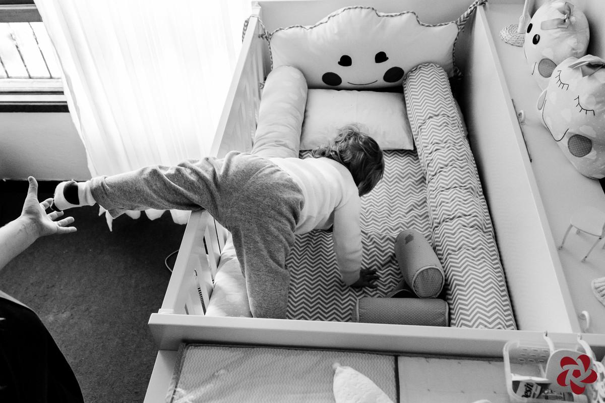 Otávio tenta sair da cama da irmã e a mãe coloca a mão para ele não cair.