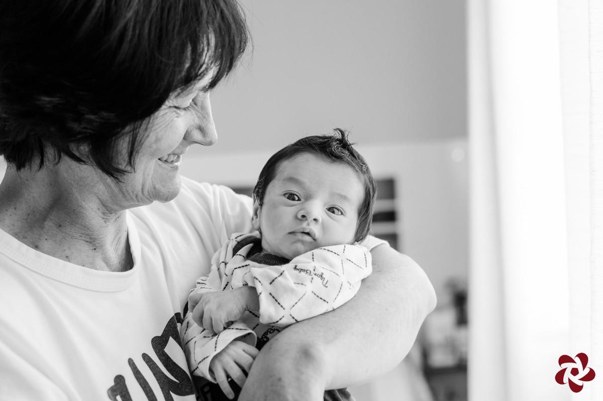 Foto em preto e branco. Após o banho Henrique está vestido e penteado no colo da avó. A avó olha para o bebê enquanto o bebê olha para a câmera fotográfica.