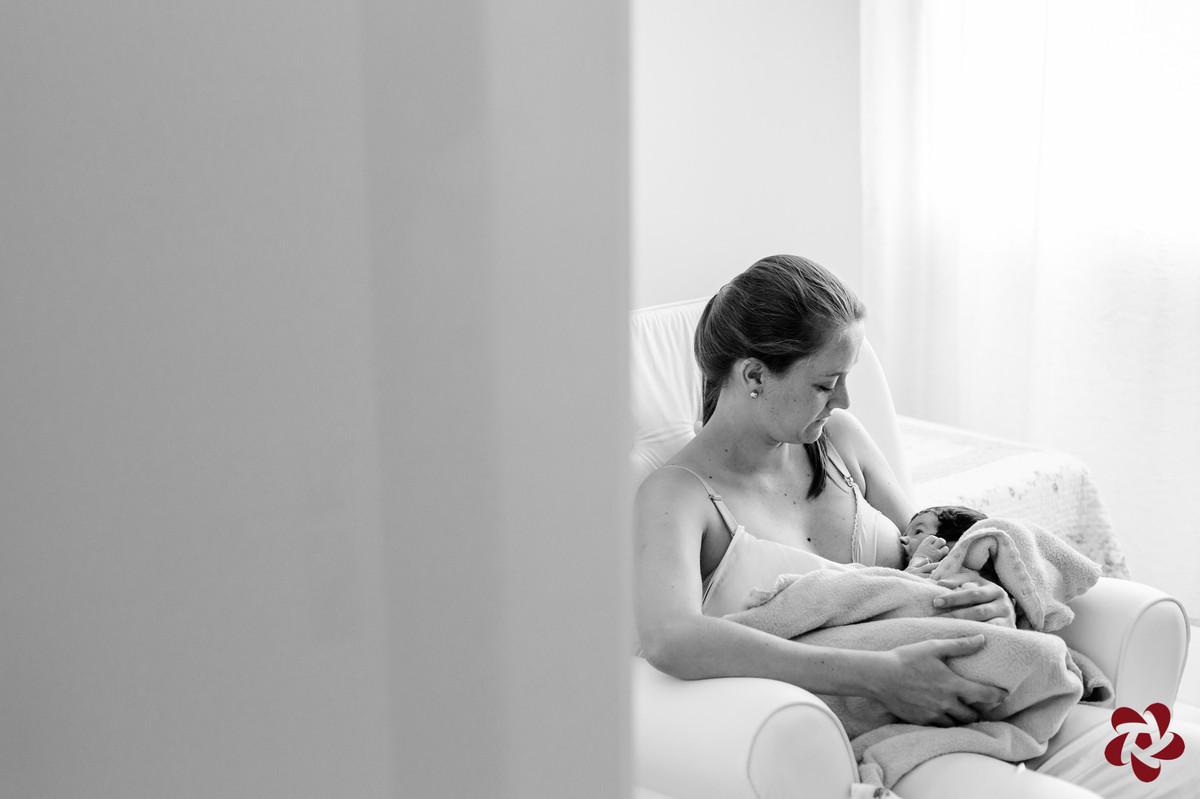 Foto em preto e branco. Katia está está no quarto sentada em uma poltrona, amamentando seu filho Henrique, que está enrolado em um cobertor, iluminados com suave luz vinda da janela