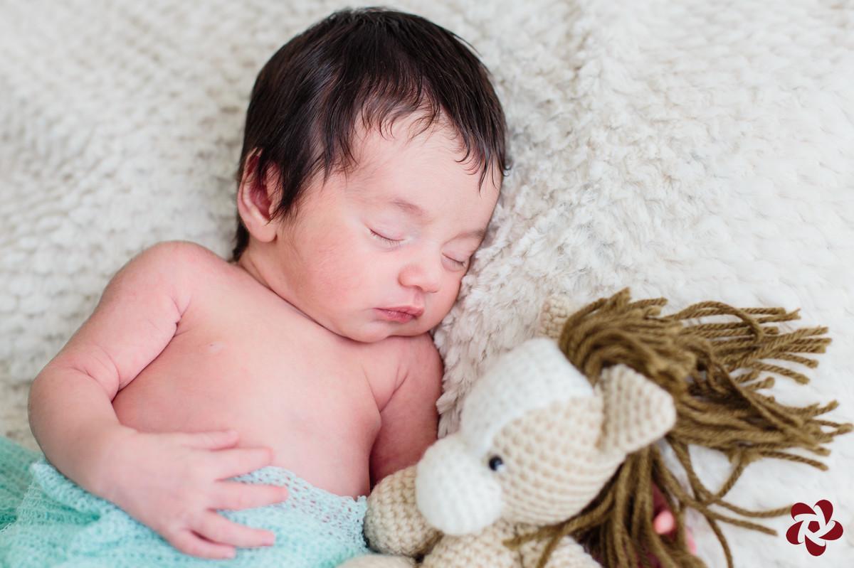 Bebê Henrique está deitando na cama em cima de um cobertor bege claro tapado com um wrap para fotos newborn verde água, abraçado em um cavalo de crochê nas cores bege, marrom e branco