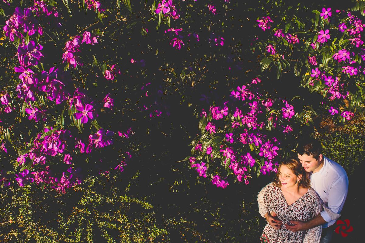 Noivos abracados ao lado flores