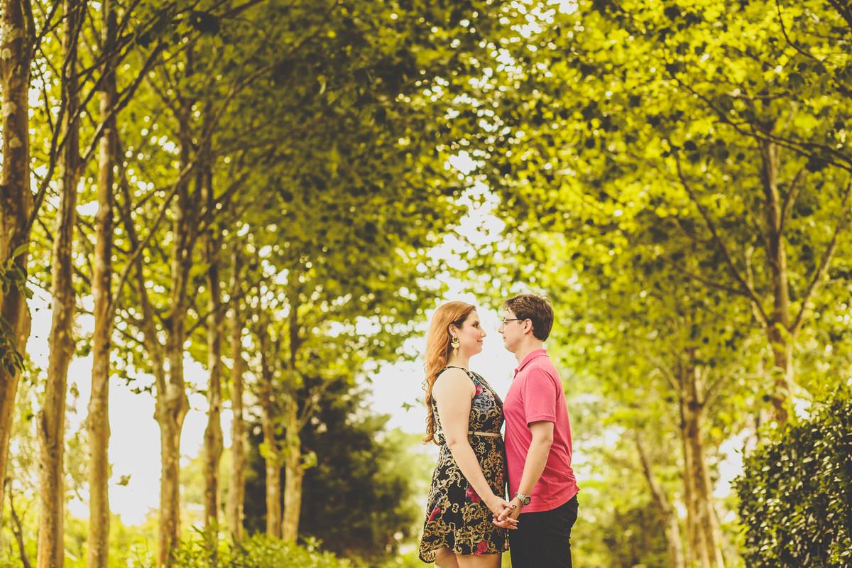 Casal de mãos dadas em meio as árvores
