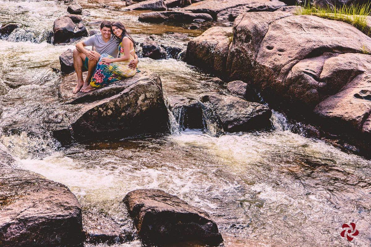 Casal sentado em cima da pedra no meio da água