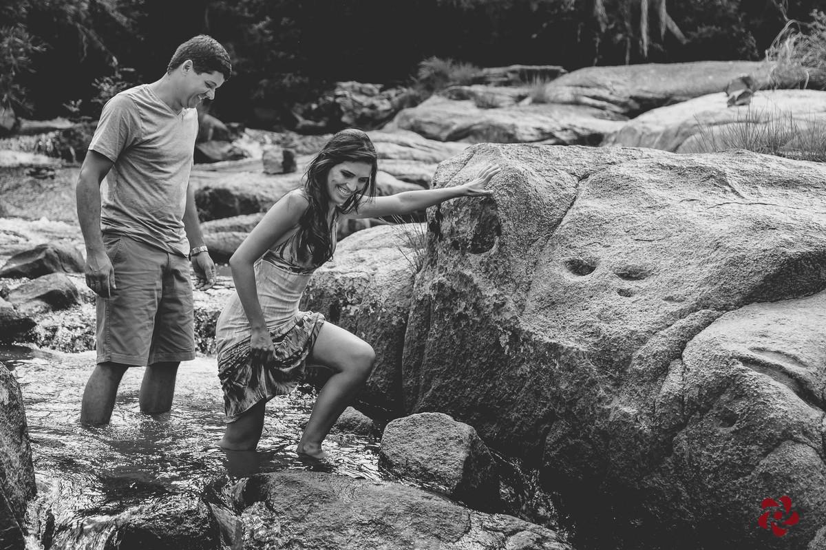 Noiva subindo na pedra e noivo sorrindo
