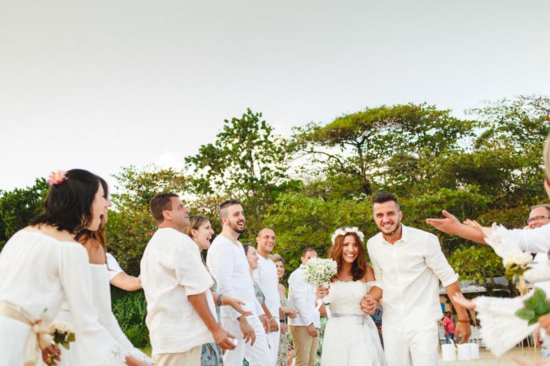 Noivos recém - casados, foto da saída dos noivos, a Mayara e o Vaz com seus padrinhos e convidados no seu casamento na praia. Fotos por Moyra e Tiago, fotógrafos de casamento