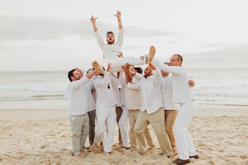Fotos divertida com os noivos e seus padrinhos. Padrinhos jogando o noivo, fotos na praia, casamento na praia. Fotos por Moyra e Tiago, fotógrafos de casamento