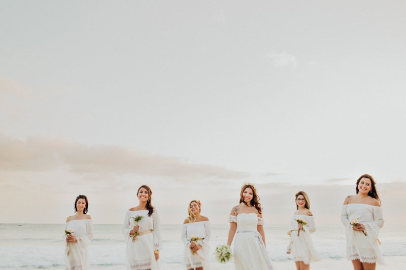 Fotos da noiva com as madrinhas. Esse casamento na praia teve uma luz incrível. A Mayara e suas amigas de branco ficaram lindas. Fotos do Tiago nesse casamento intimista. Casamento em São Sebastião na Praia de Santiago.