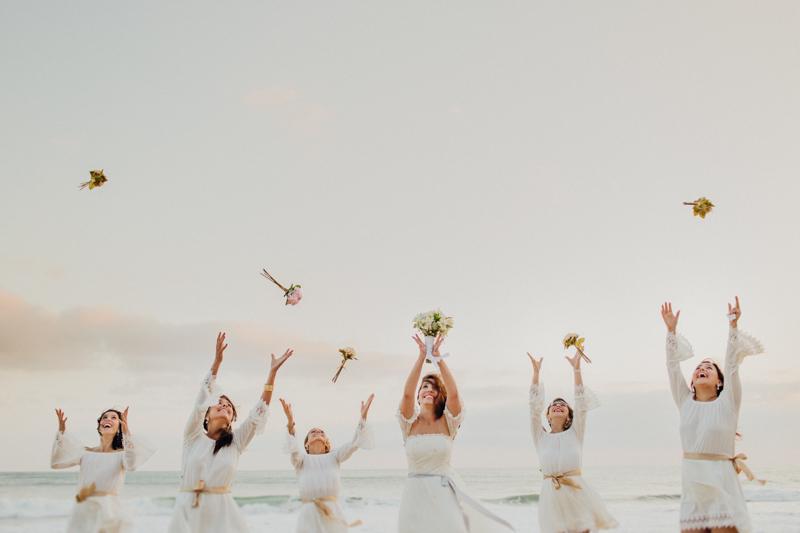 As madrinhas com a noiva, numa foto bem divertida. A noiva e as madrinhas são jogando o buquê, num lindo cenário num casamento na praia. Fotos por Moyra e Tiago, fotógrafos de casamento.