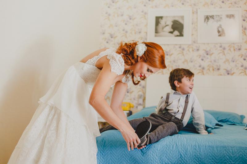 A noiva Helena se arrumou em casa junto com seus filhos. Depois da noiva estar pronta ela ajudou a preparar seus filhos para o casamento. A noiva arrumando o seu filho antes do casamento.
