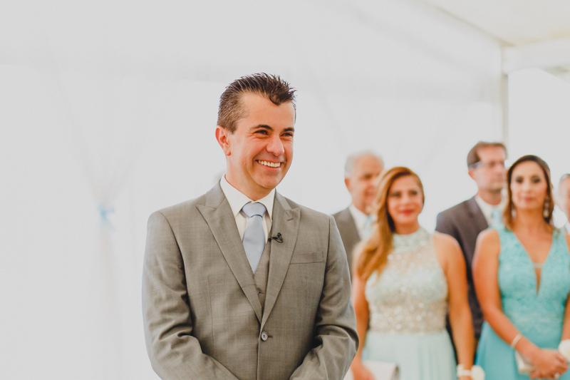 Quando a noiva entrou pelo corredor o noivo ficou bastante sorridente. A expressão do noivo revela toda a emoção desse momento. Fotografia de casamento, fotos de casamento, noiva pó de arroz, vestido de noiva , vestida de branc