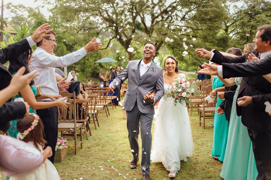foto de saída dos noivos Paula e Mailson. Os noivos receberam uma chuva de pétalas de flores.