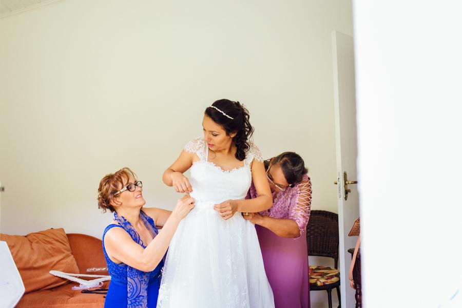 A noiva contou com a ajuda de sua mãe e sua sogra. Elas ajudaram a Paula a colocar seu vestido de noiva.
