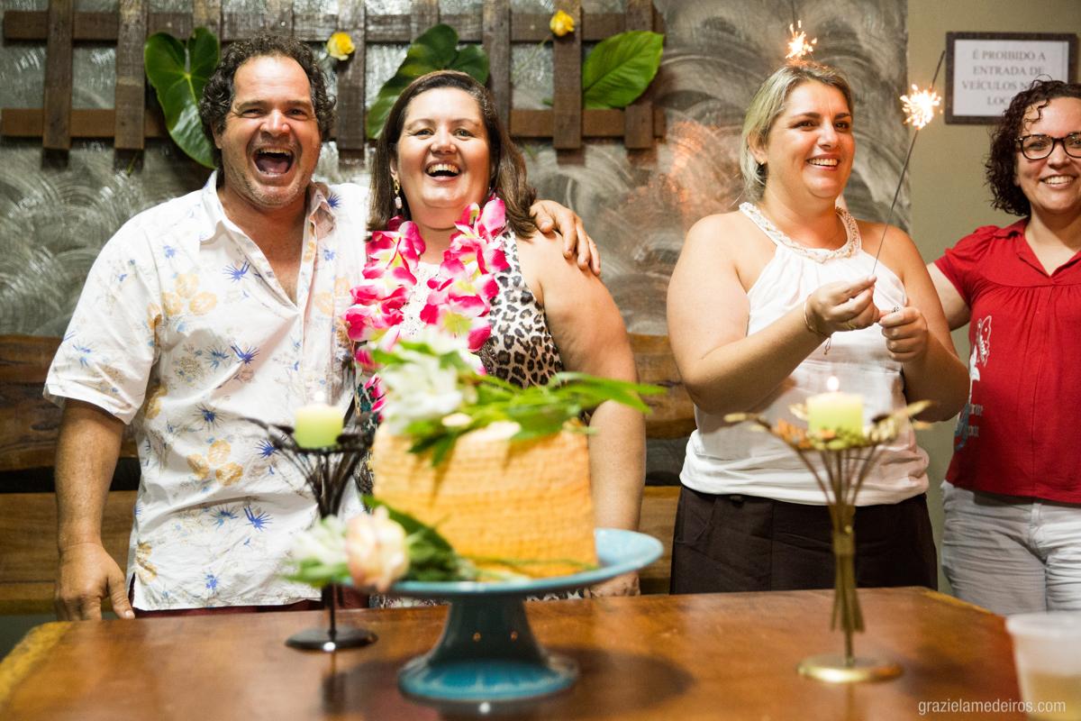 cantando parabens na mesa do bolo com seu marido em sua festa de aniversario
