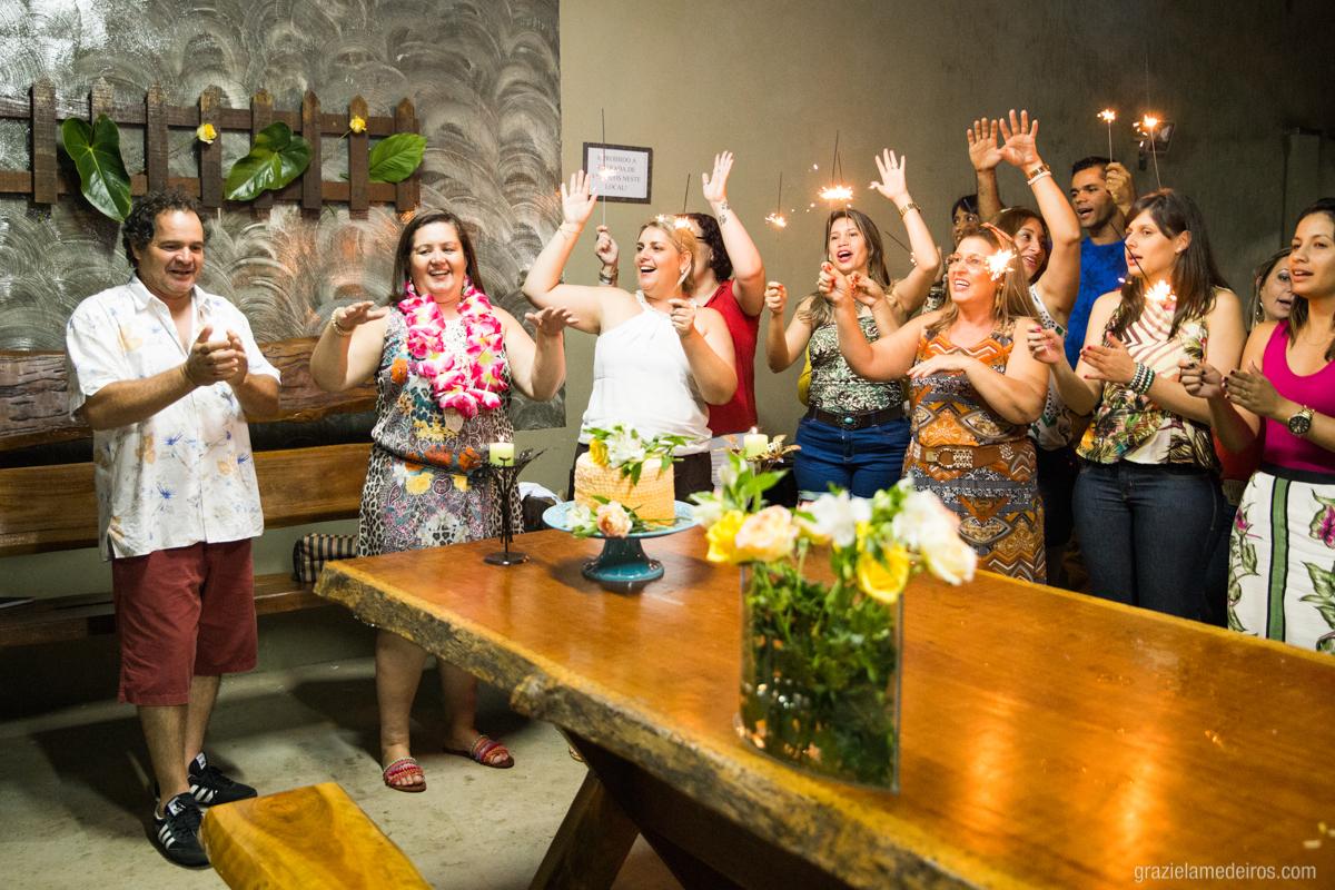 cantando parabens na mesa do bolo com seu marido e amigos em sua festa de aniversario