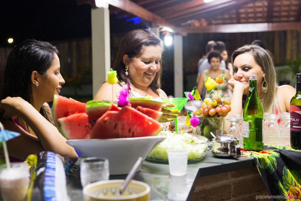aniversariante na mesa de drinks rindo com convidados