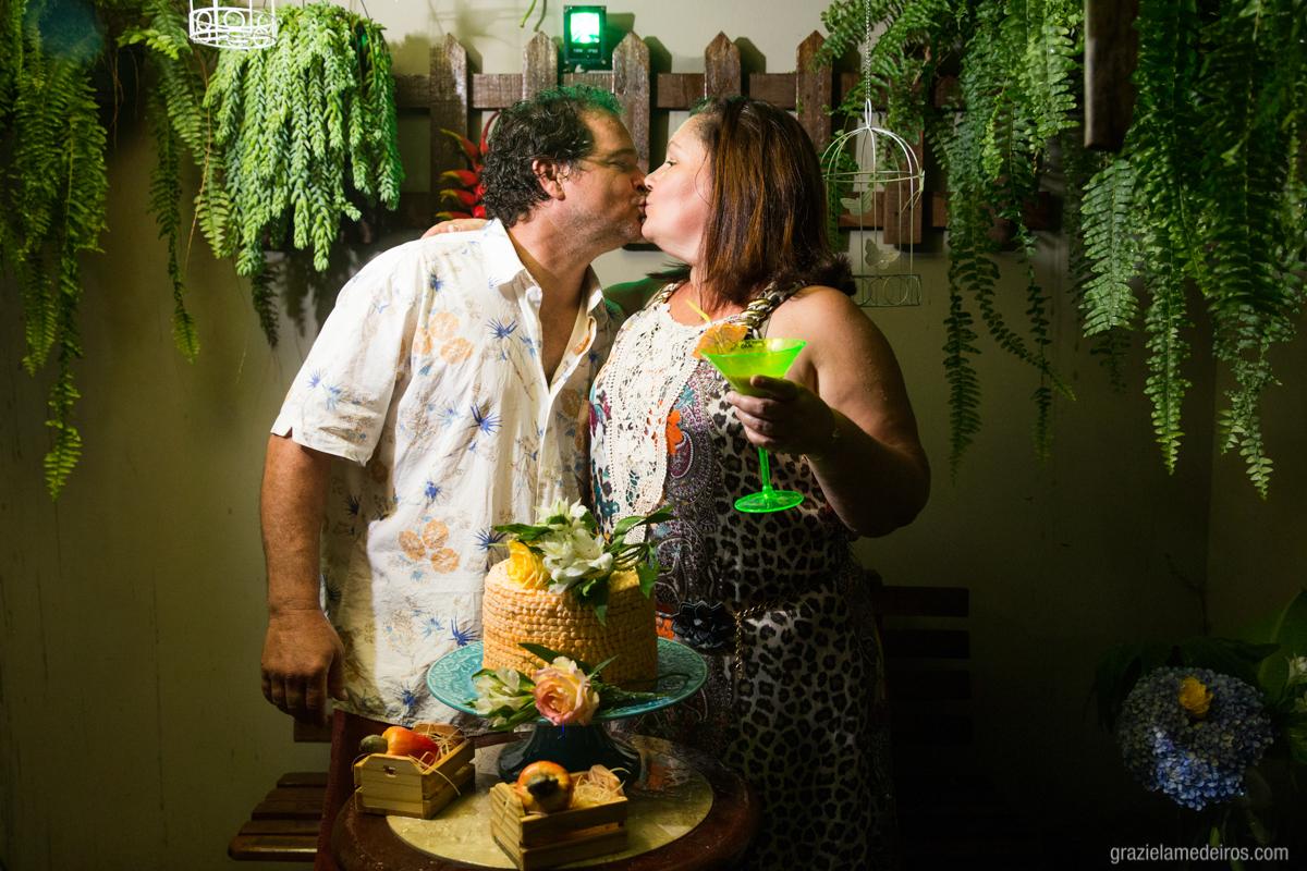 aniversariante beijando seu marido na mesa do bolo