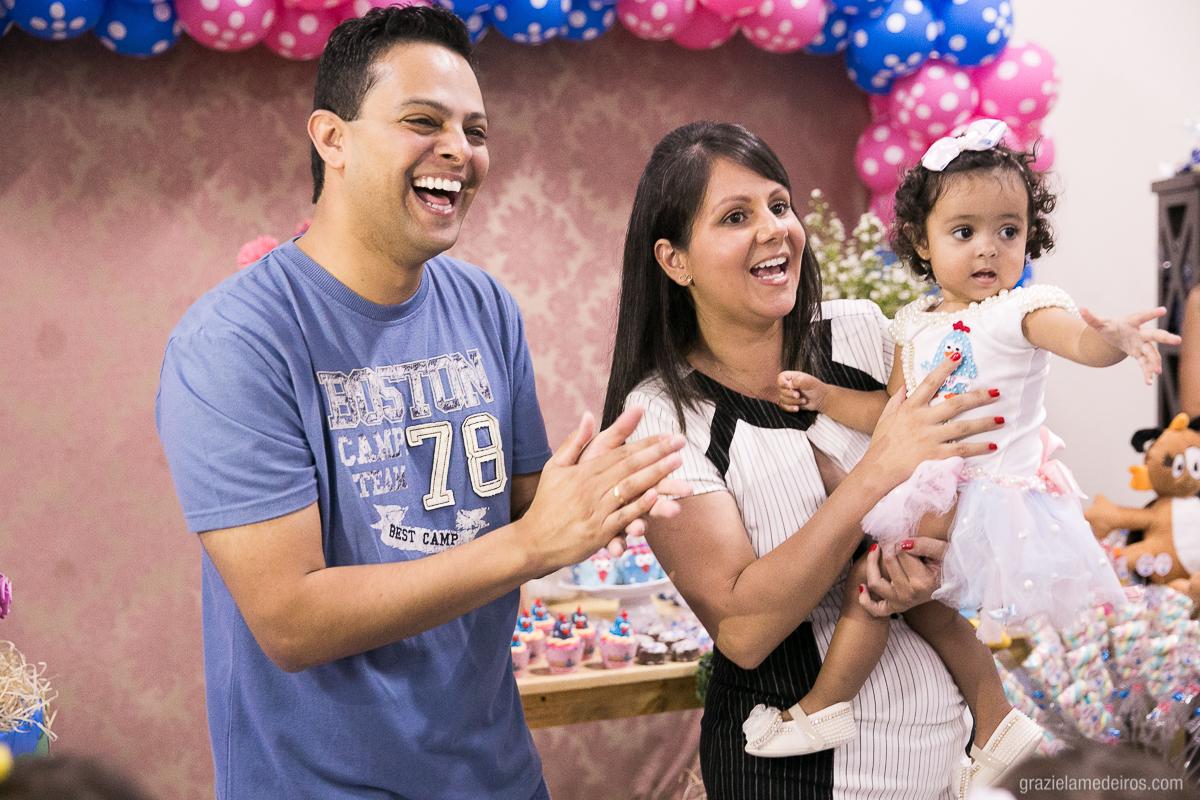 criança com os pais cantando parabens em sua festa de aniversario com o tema galinha pintadinha