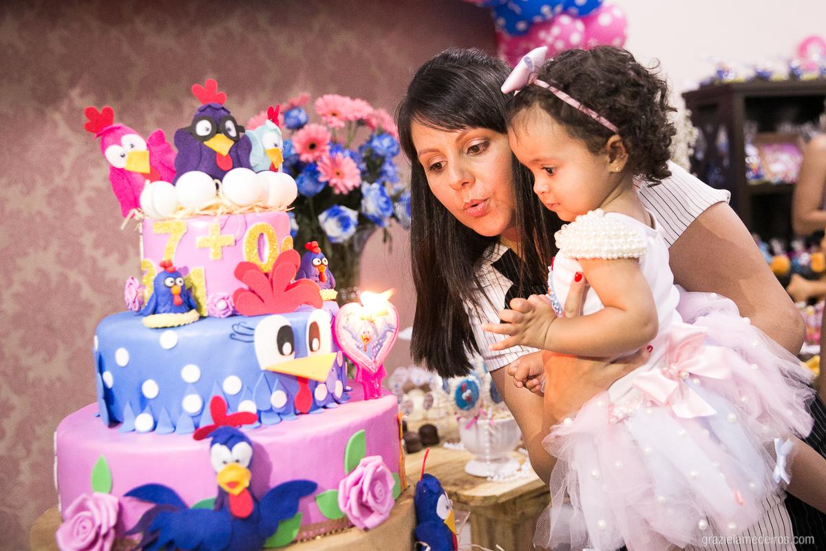 criança no bolo da mae apagando a velinha depois de cantar parabens em sua festa de aniversario com o tema galinha pintadinha