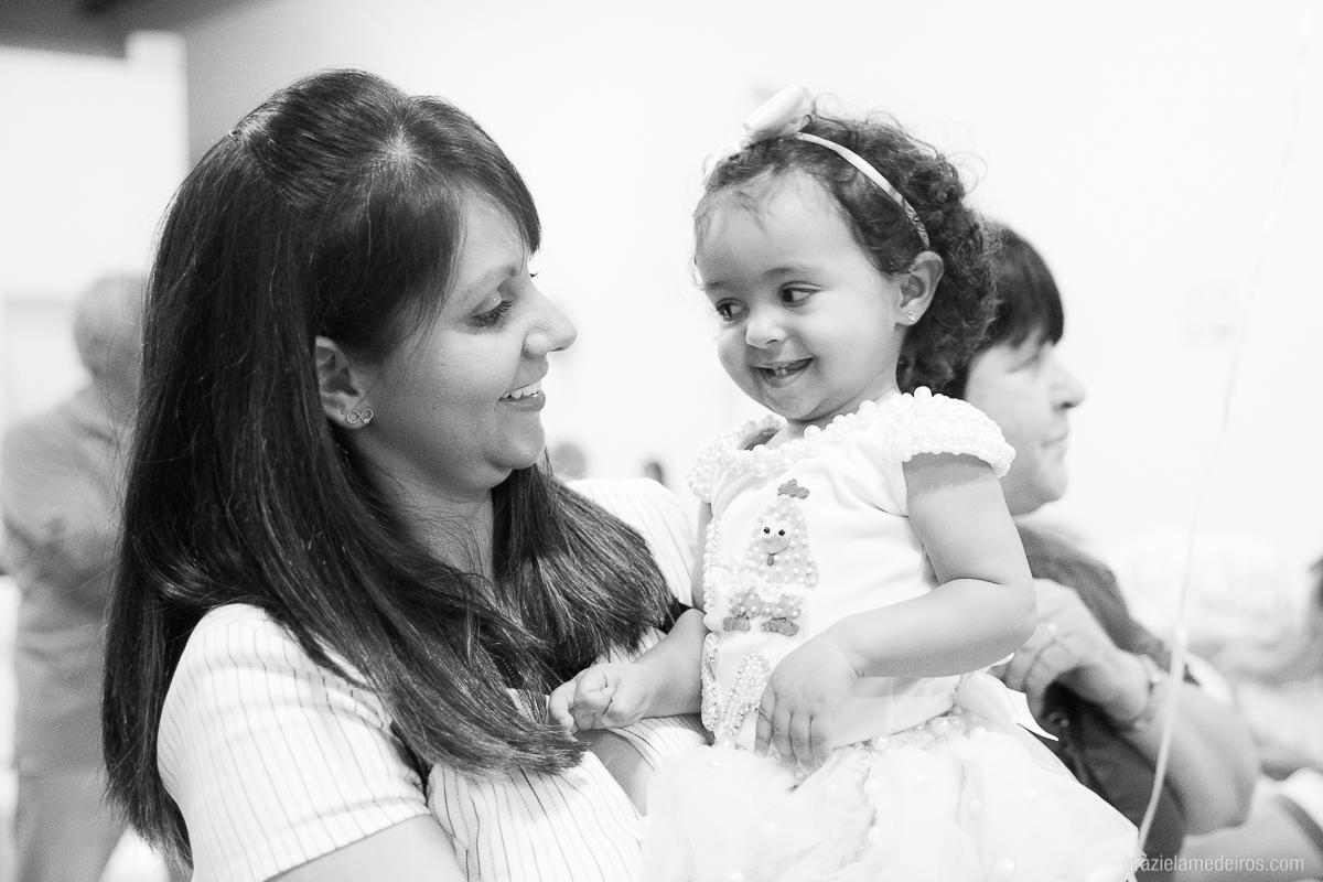 criança sorrindo no colo da mae na sua festa de aniversario