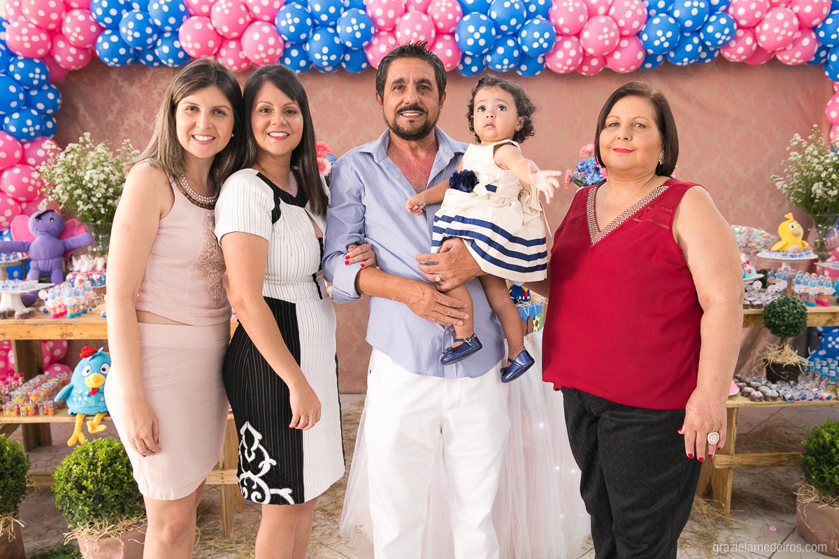 foto com a familia na mesa do bolo na festa de aniversario com o tema galinha pintadinha