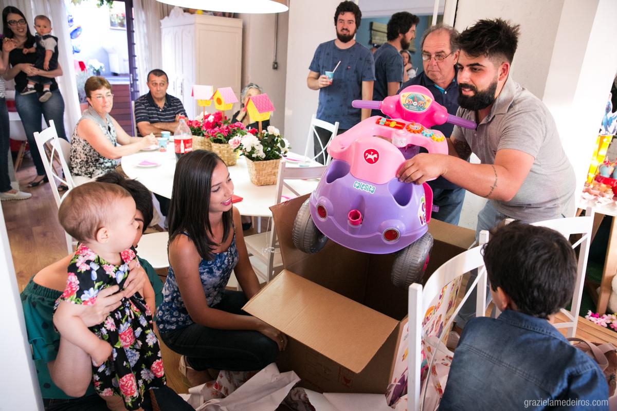 familiares olhando criança ganhar brinquedo do tio em seu aniversario de um aninho em guaxupe