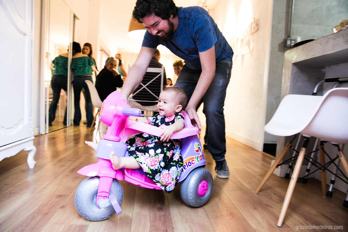criança brincando com o pai de velotrol em seu aniversario de um aninho em guaxupe