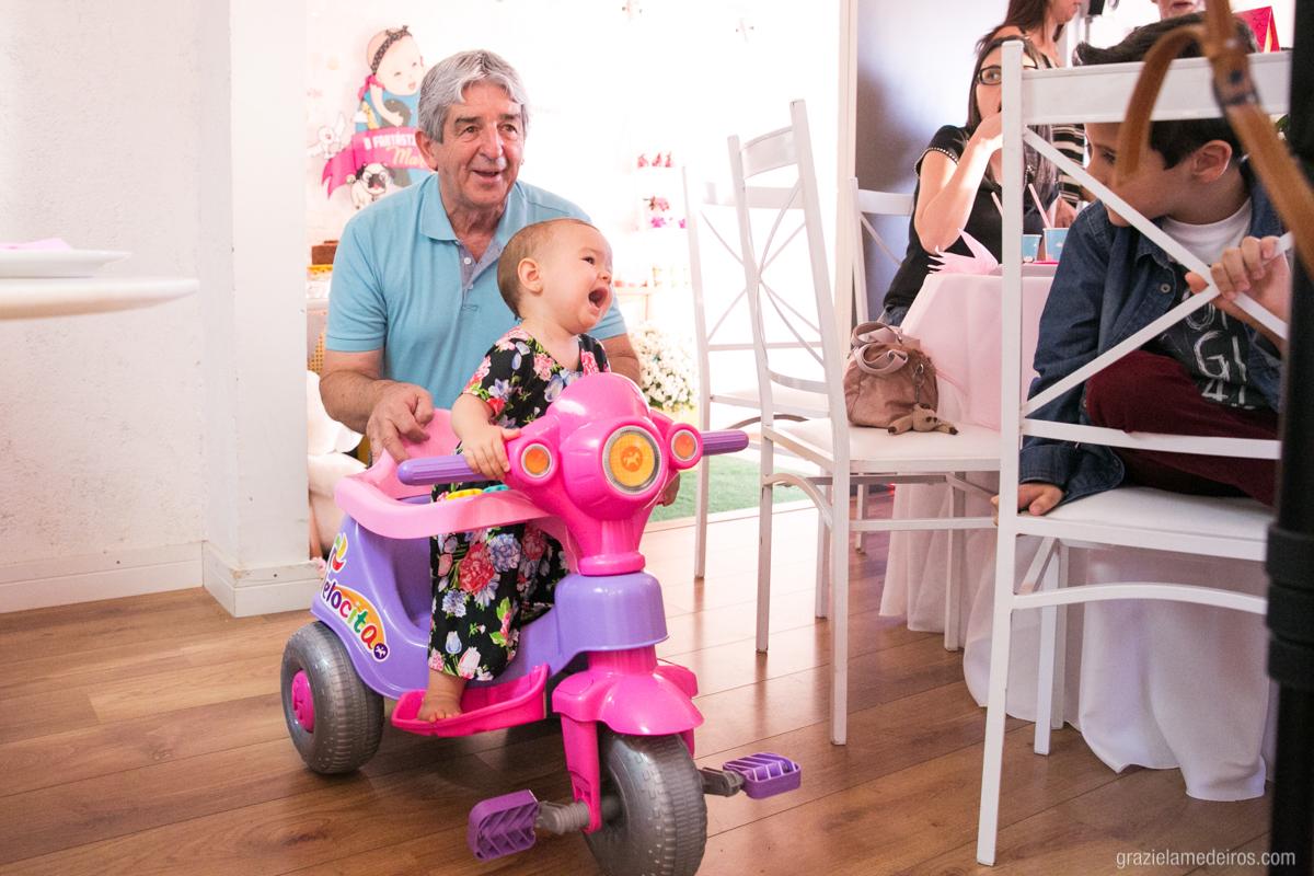 criança brincando no velotrol com seu avo em seu aniversario de um aninho em guaxupe