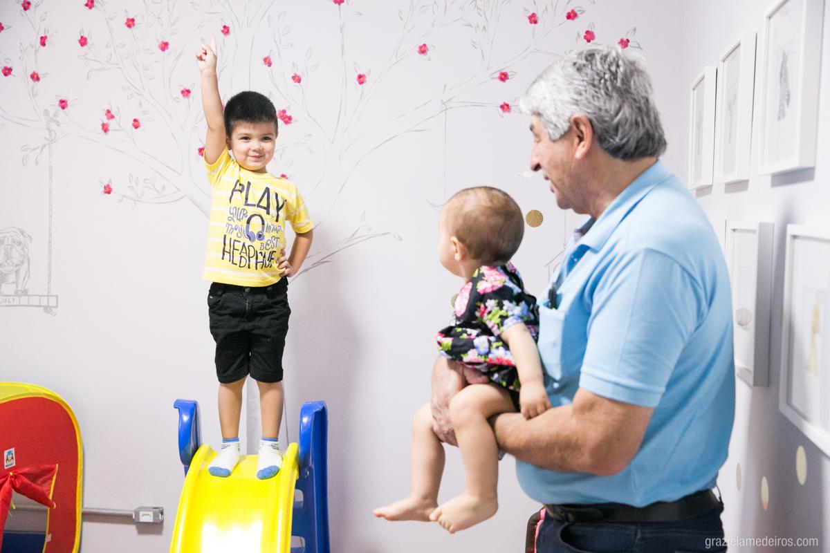 criança brincando no seu quarto com seu avo em aniversario de um aninho em guaxupe