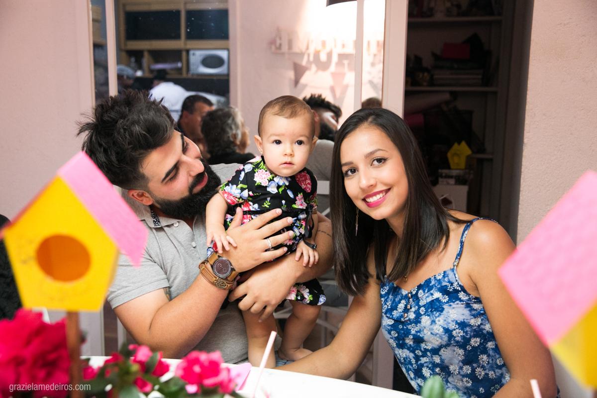 aniversariante no colo do tio e madrinha em seu aniversario de um ano em guaxupe