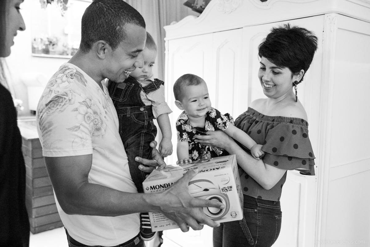 criança recebendo presente no colo da mae em seu aniversario de um aninho em guaxupe