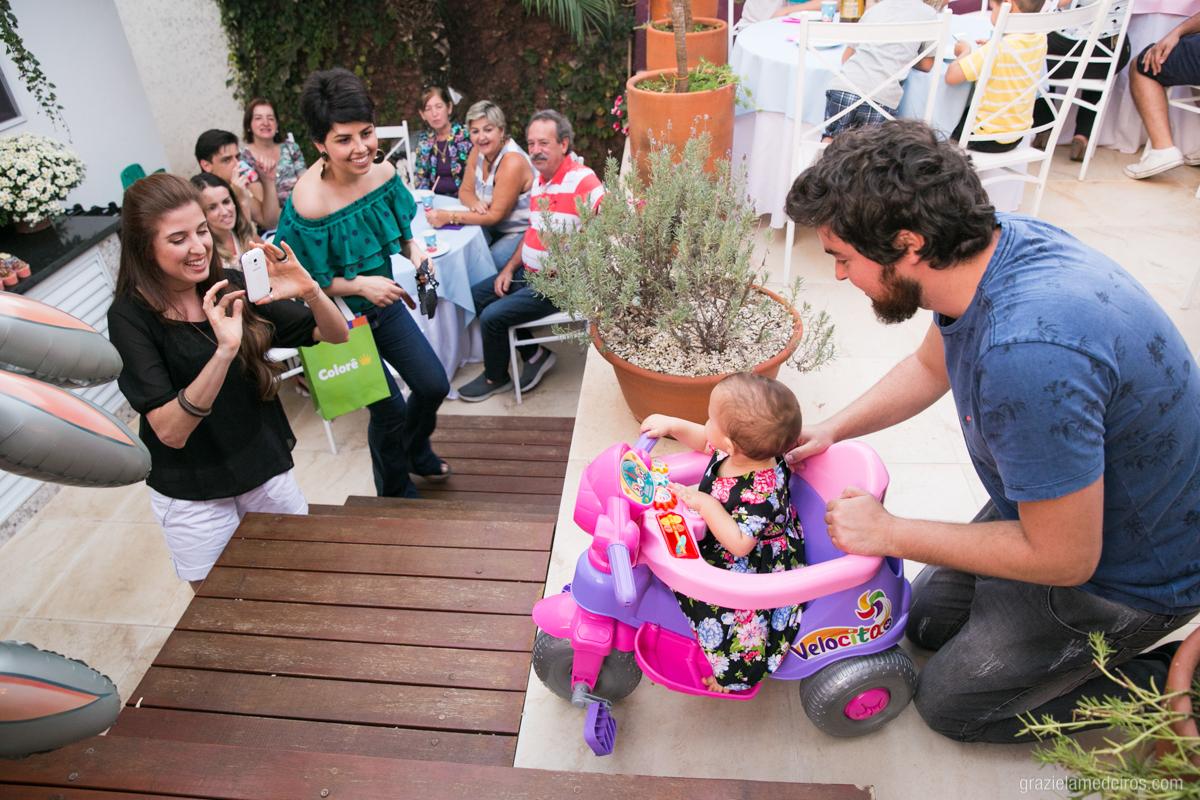 criança brincando no velotrol com seu pai no quintal da casa sendo fotografada por convidados em seu aniversario de um ano em guaxupe