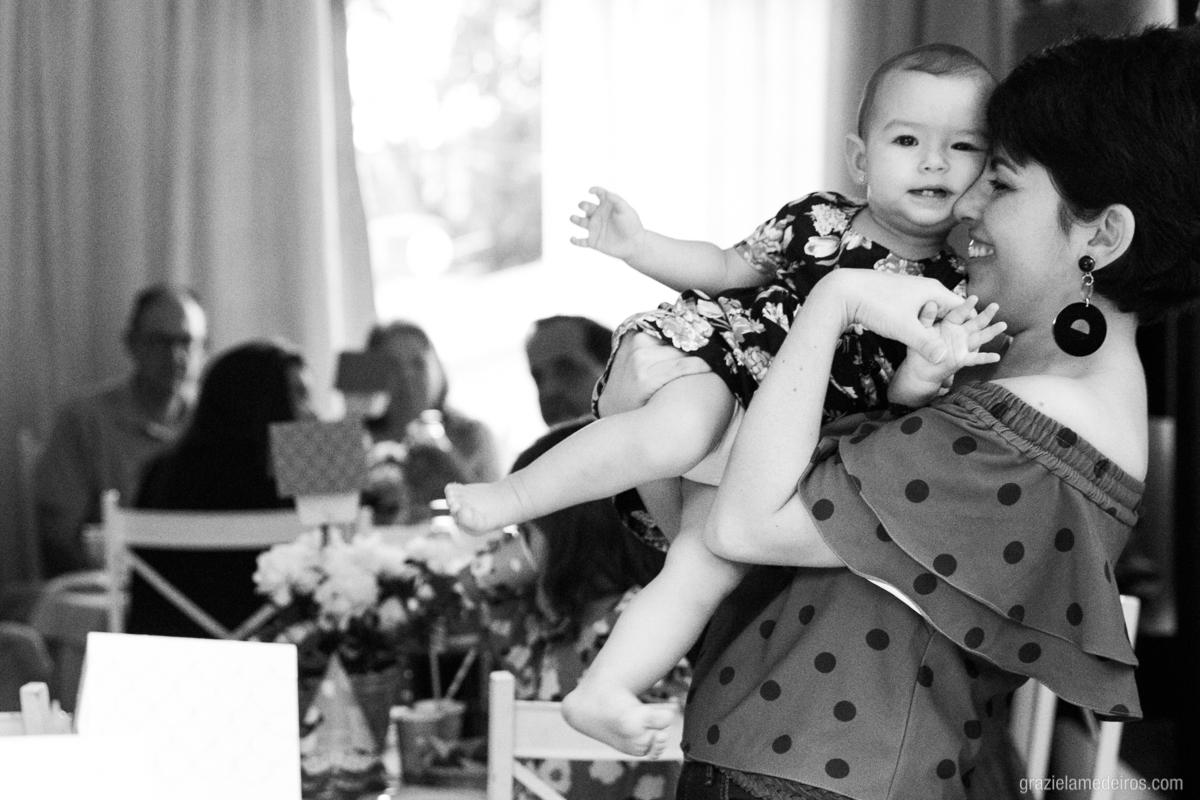 crinança brincando no colo da mae em seu aniversario de um ano em guaxupe