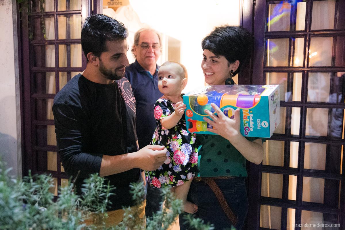 criança no colo da mae ganhando presente do tio em seu aniversario de um ano em guaxupe