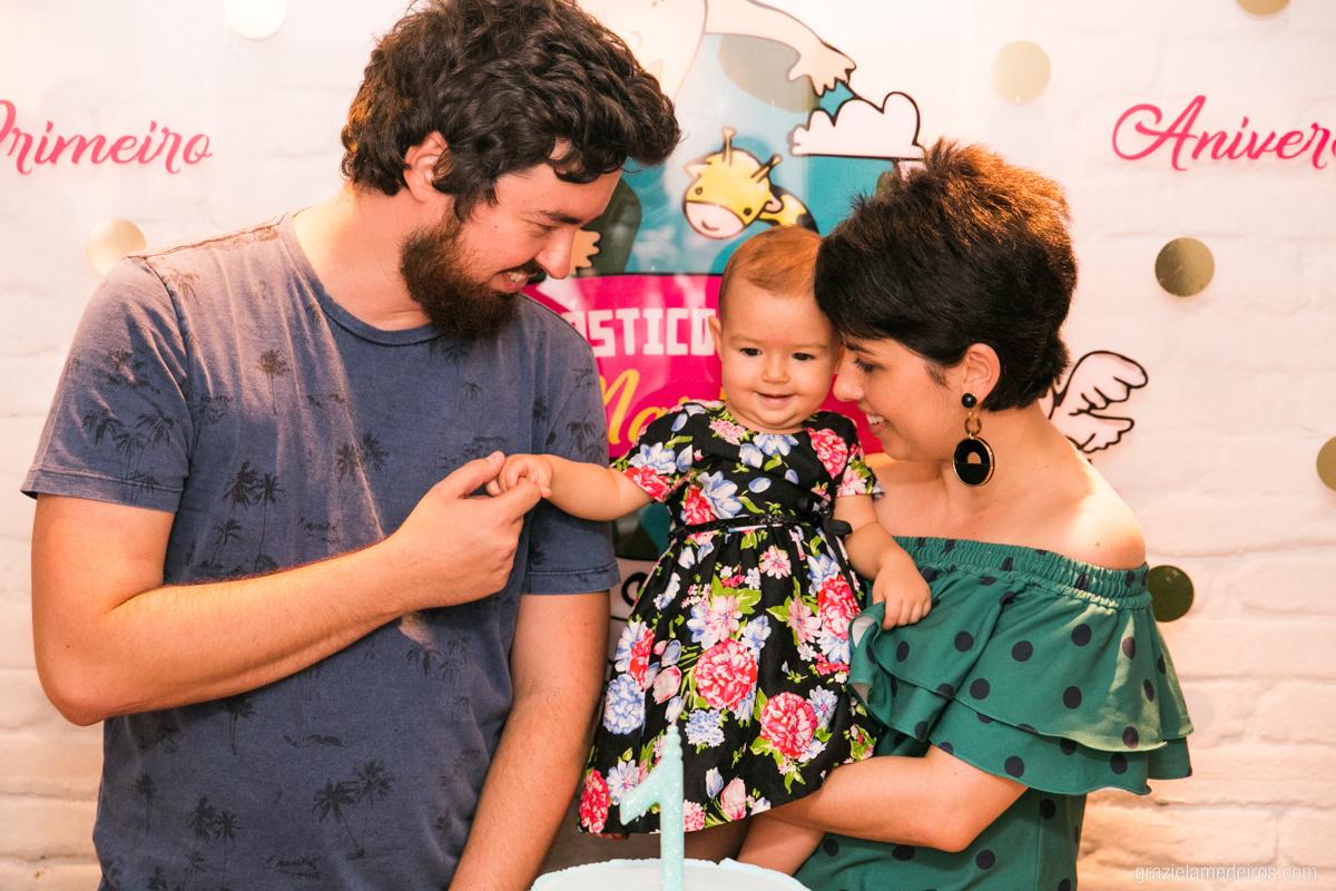 criança na mesa do bolo cantando parabens com os pais em seu aniversario de um ano em guaxupe