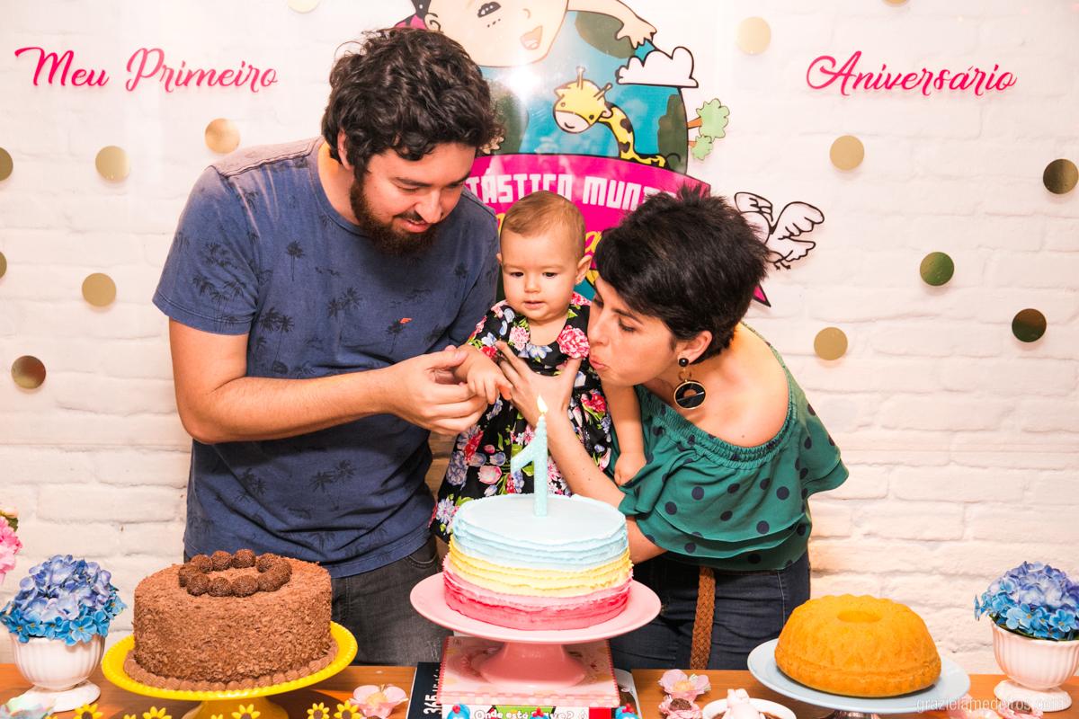 criança assoprando velinha de aniversario com seus mais em seu primeiro aninho em guaxupe