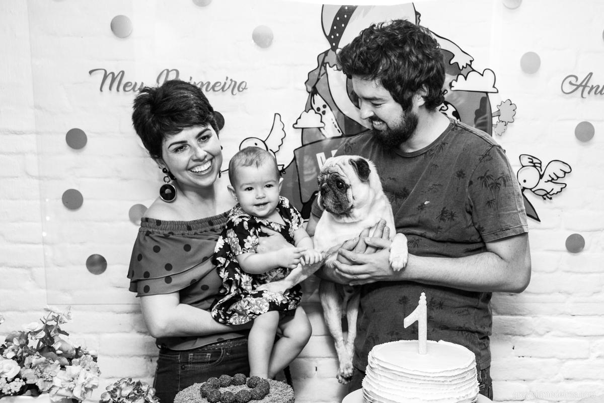 criança na mesa do bolo cantando parabens com os pais e seu cachorro de estimacao em seu aniversario de um ano em guaxupe