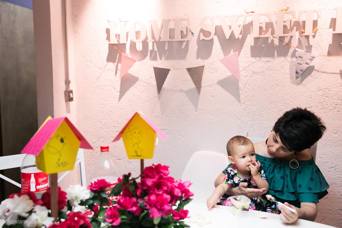 criança comendo bolo com sua mae em seu aniversario de um aninho em guaxupe