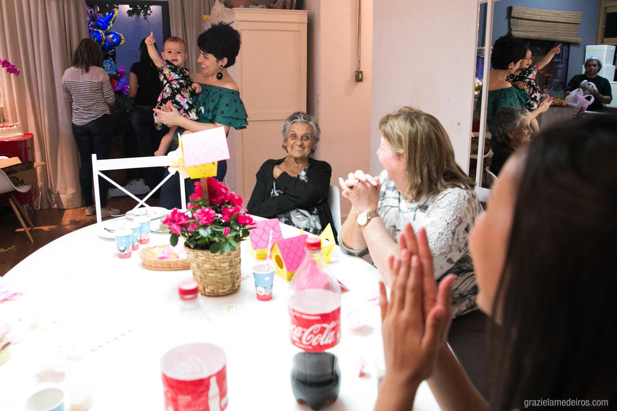 criança no colo da mae brincando com convidados em seu aniversario de um ano em guaxupe