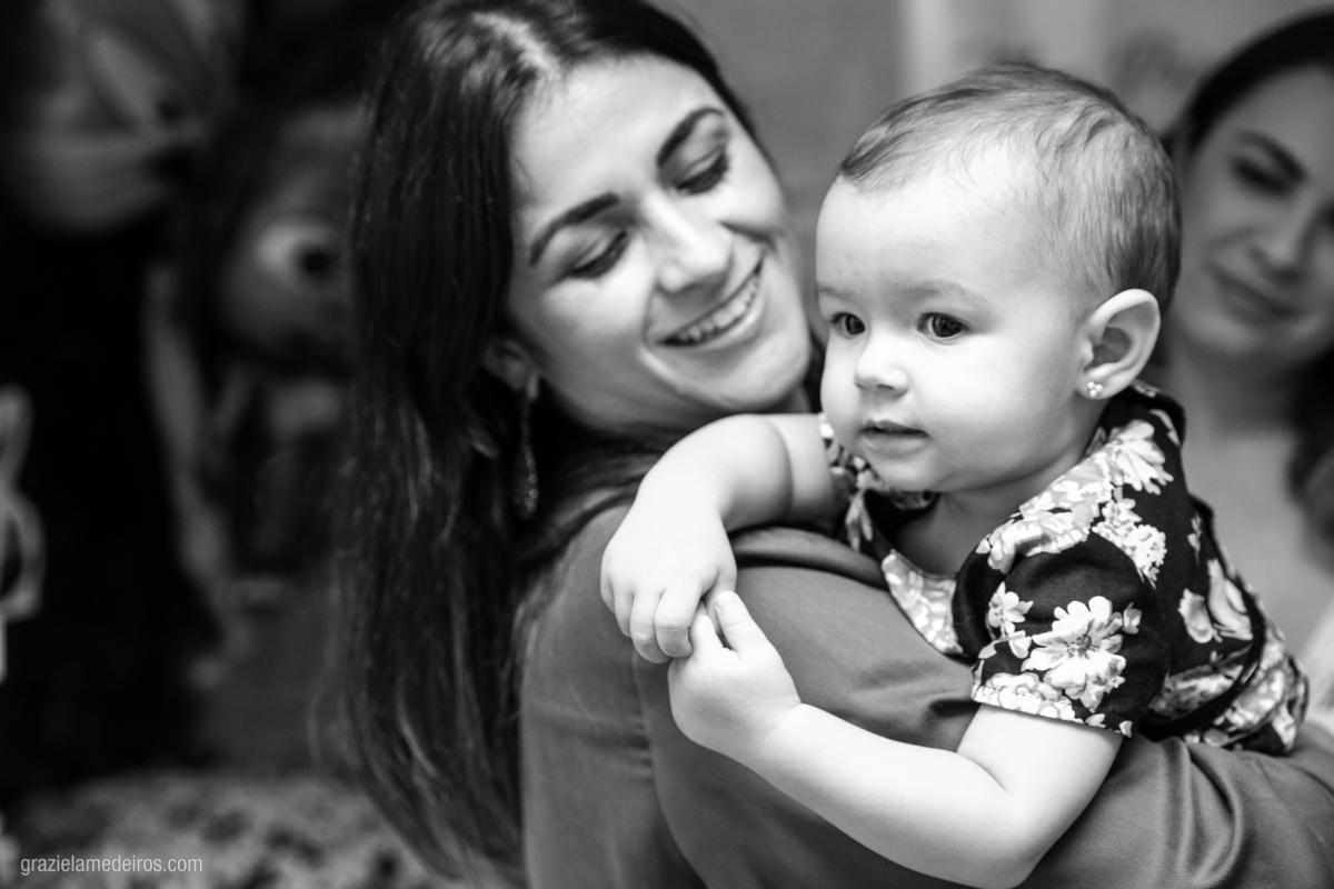 criança no colo da tia em seu aniversario de um aninho em guaxupe
