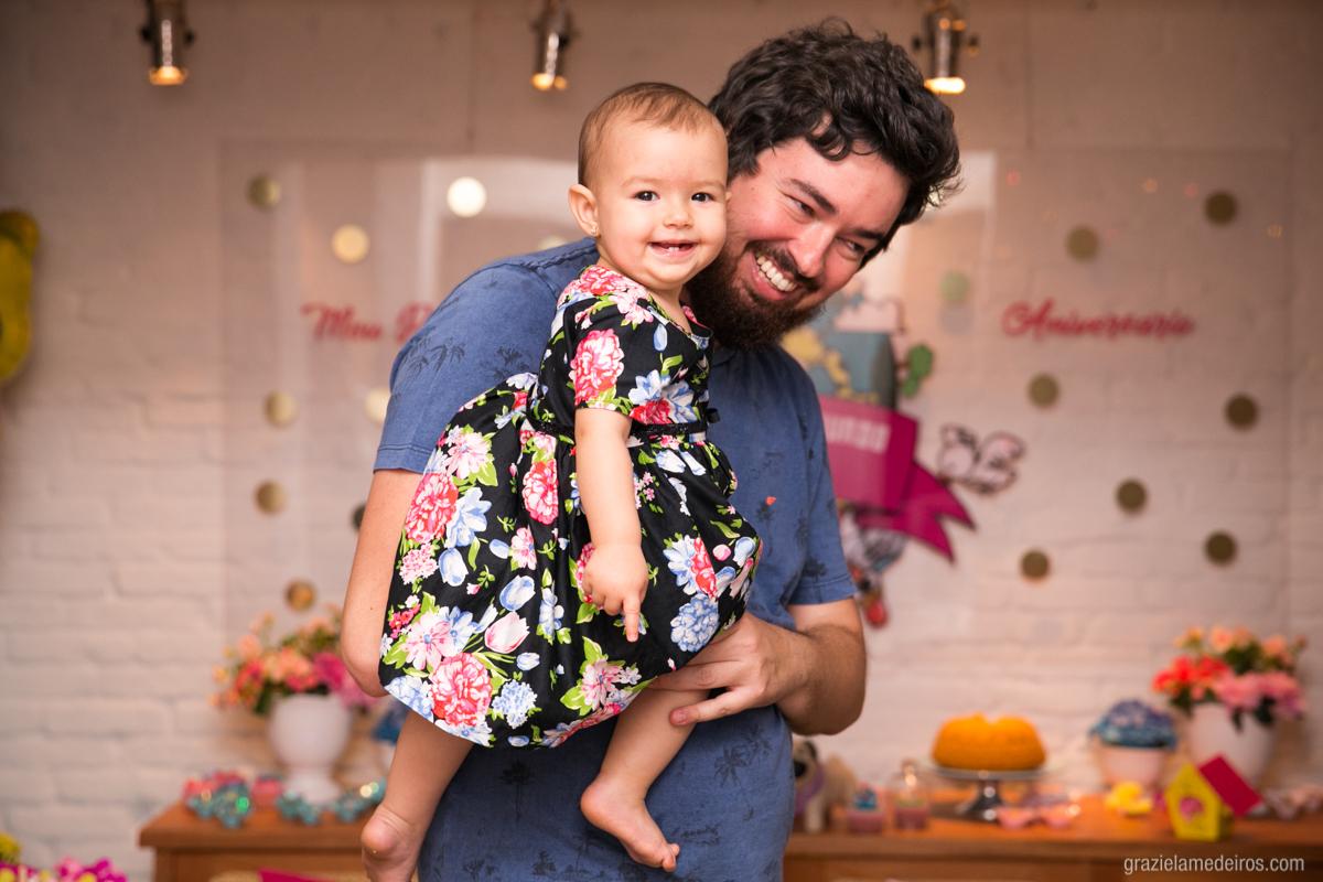 criança brincando e sorrindo no colo do pai em seu aniversario de um ano em gauxupe