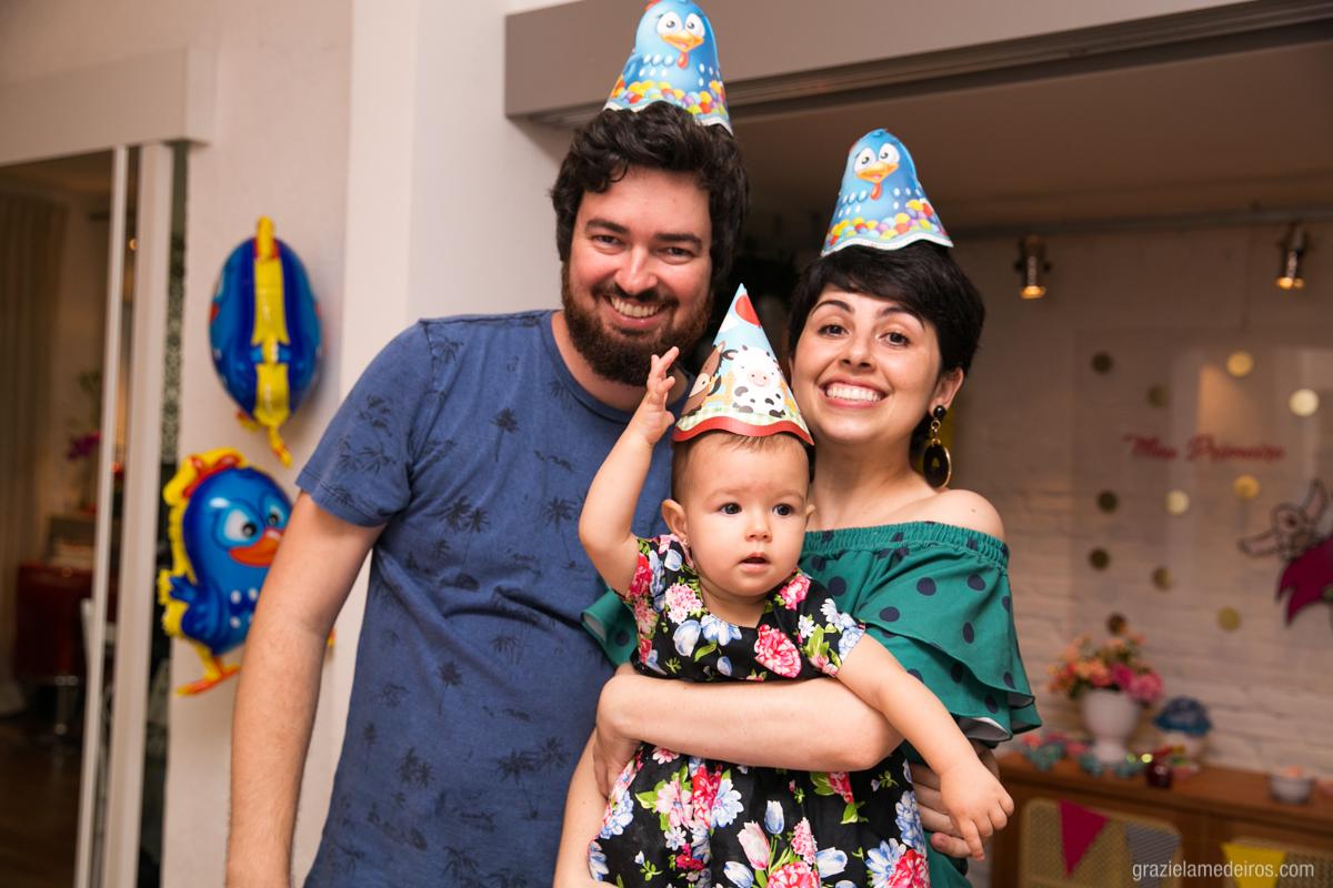 criança com os pais de chapeu de aniversario em seu aniversario de um ano em guaxupe
