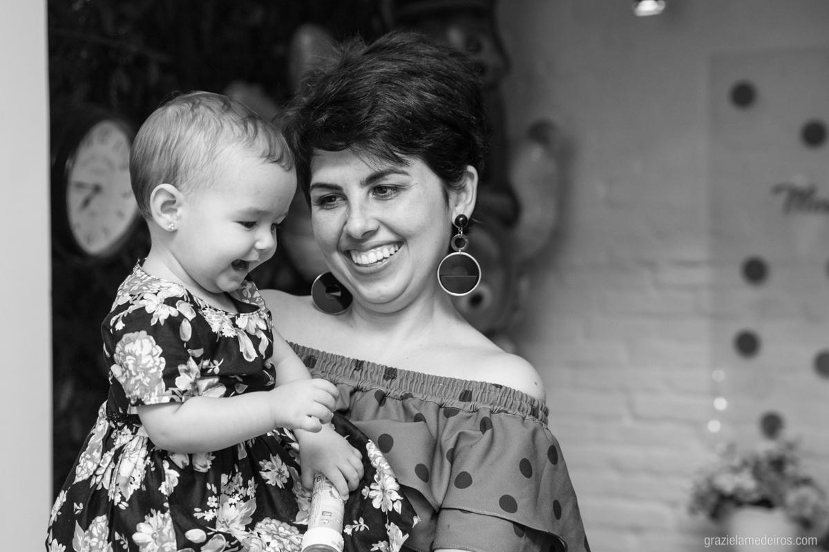 criança no colo da mae sorrindo em seu aniversario de um ano em guaxupe