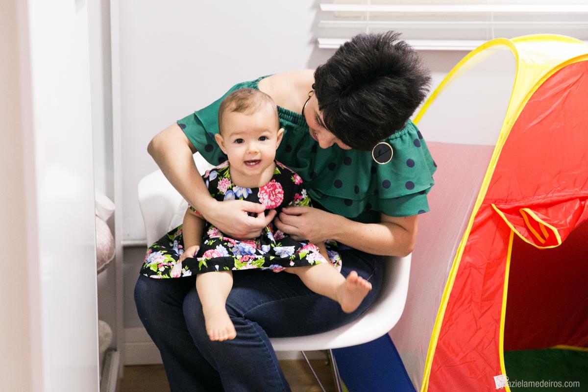 aniversariante no colo da mae se preparando para seu primeiro aniversario em guaxupe