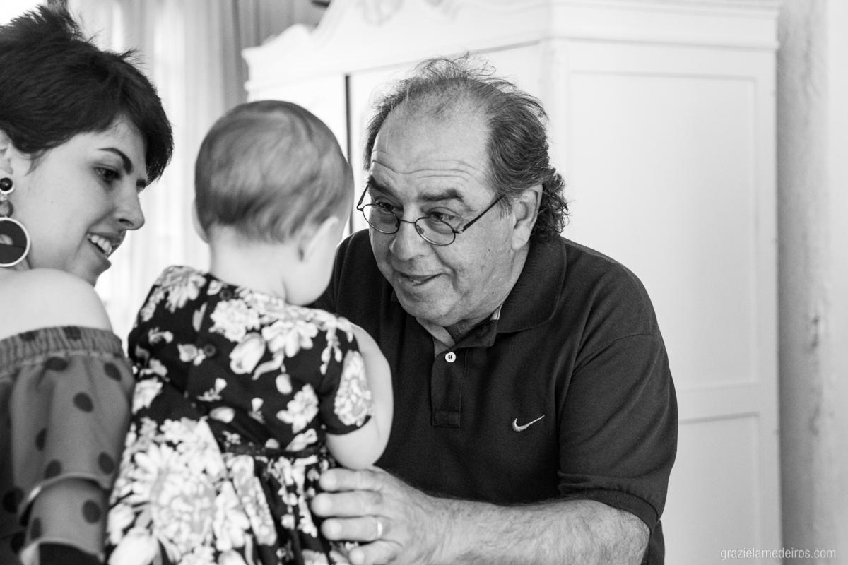 avo pegando criança do colo da mae em seu aniversaio de um aninho em guaxupe
