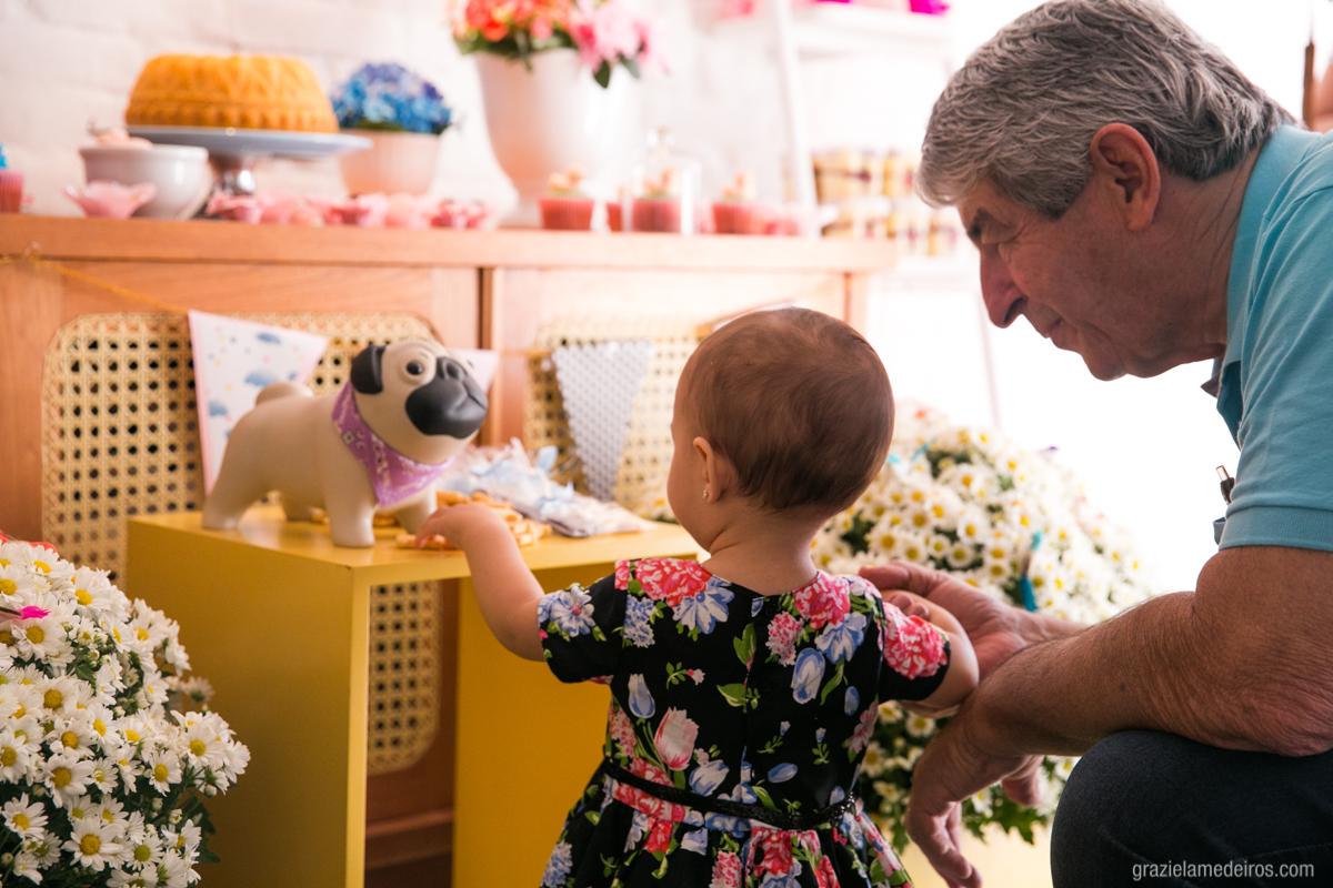 crianca pegando doces da mesa do bolo com seu avo em seu primeiro aniversario em guaxupe
