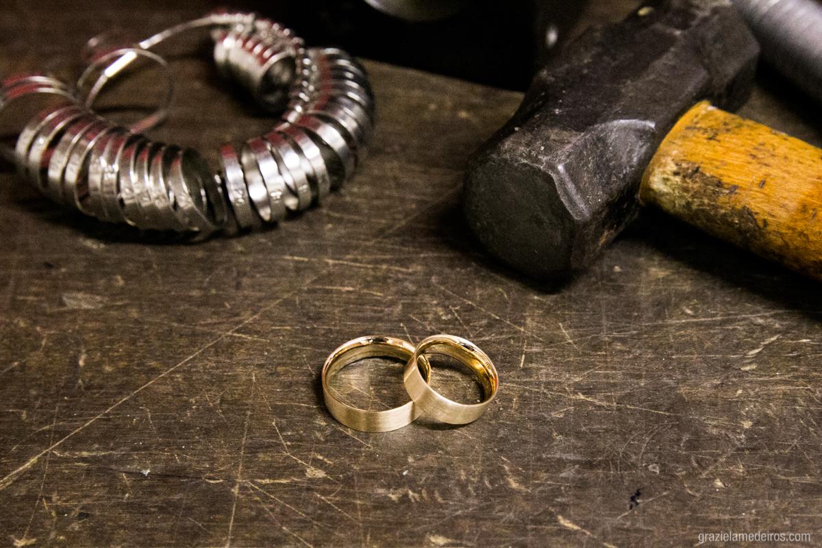 alianças de casamento na bancada com ferramentas do atelie labriola